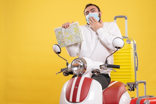 Vista superior del concepto de viaje con chico confundido en máscara médica de pie cerca de la motocicleta con maleta amarilla y sosteniendo el mapa