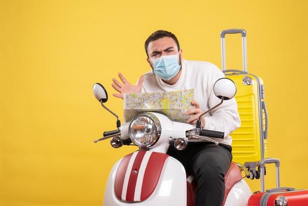 Vista superior del concepto de viaje con un chico desconcertado con máscara médica sentado en una motocicleta con una maleta amarilla y sosteniendo un mapa