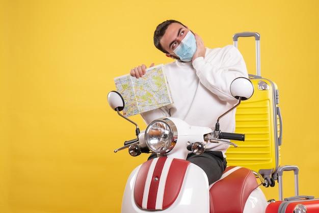 Vista superior del concepto de viaje con chico de ensueño en máscara médica de pie cerca de la motocicleta con maleta amarilla y sosteniendo el mapa