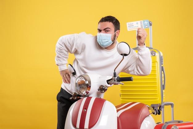 Vista superior del concepto de viaje con chico joven en máscara médica de pie junto a la motocicleta con maleta amarilla y sosteniendo el boleto