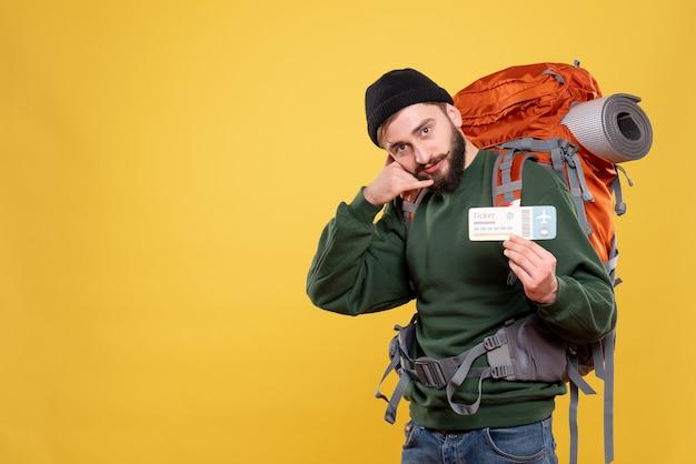 Vista superior del concepto de viaje con chico joven con packpack y haciendo gesto de llamarme