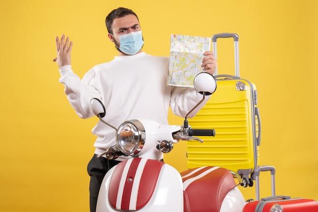Vista superior del concepto de viaje con chico nervioso en máscara médica de pie cerca de la motocicleta con maleta amarilla y sosteniendo el mapa