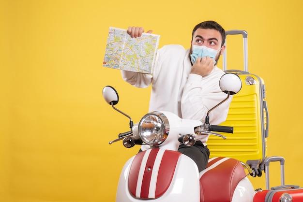 Vista superior del concepto de viaje con chico pensante en máscara médica de pie cerca de la motocicleta con maleta amarilla y sosteniendo el mapa