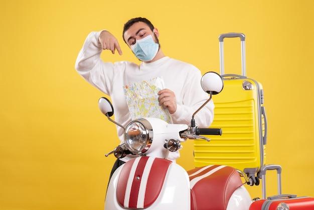 Vista superior del concepto de viaje con chico seguro en máscara médica de pie cerca de motocicleta con maleta amarilla y mapa señalando