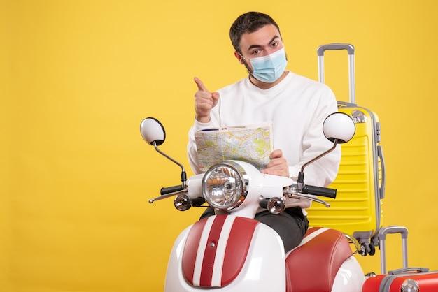 Vista superior del concepto de viaje con chico seguro en máscara médica de pie cerca de la motocicleta con maleta amarilla y sosteniendo el mapa apuntando hacia adelante