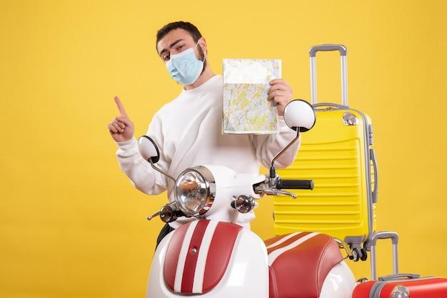Vista superior del concepto de viaje con chico seguro en máscara médica de pie cerca de la motocicleta con maleta amarilla y sosteniendo el mapa apuntando hacia arriba