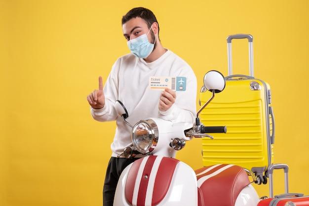 Vista superior del concepto de viaje con chico sonriente en máscara médica de pie cerca de la motocicleta con maleta amarilla y sosteniendo el boleto apuntando hacia arriba