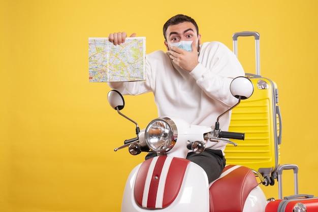 Vista superior del concepto de viaje con chico sorprendido en máscara médica de pie cerca de la motocicleta