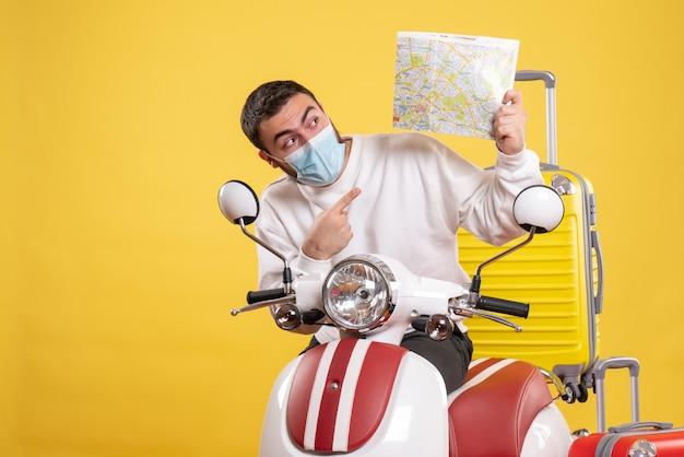 Vista superior del concepto de viaje con un tipo curioso en una máscara médica de pie cerca de la motocicleta con una maleta amarilla y un mapa señalando