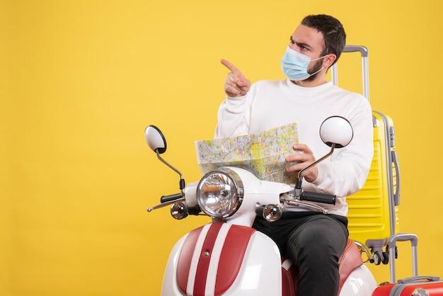 Vista superior del concepto de viaje con un tipo curioso con máscara médica sentado en una motocicleta con una maleta amarilla y sosteniendo un mapa