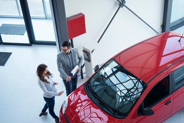 Vista superior del concesionario de automóviles que presenta un automóvil nuevo al cliente.