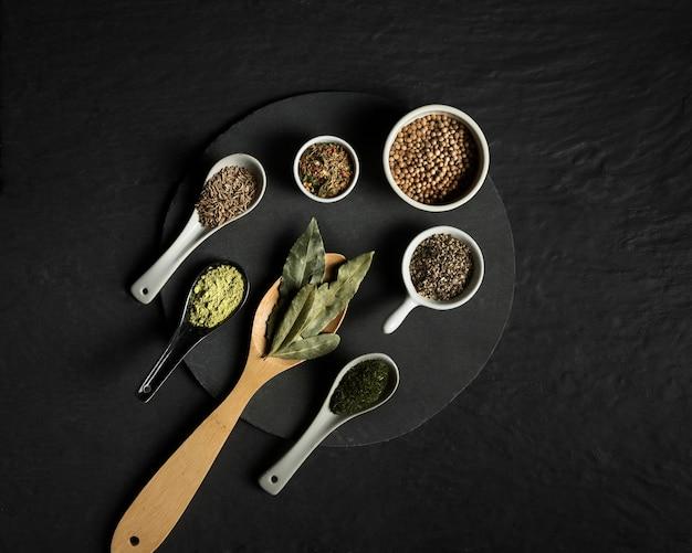 Vista superior condimentos especias en cucharas de madera