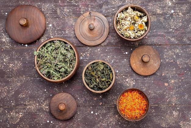 Una vista superior de condimentos picantes secos de diferentes colores dentro de tazones sobre el escritorio marrón verde menta seca