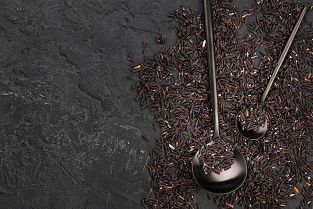 Vista superior de condimentos en pizarra con cucharas
