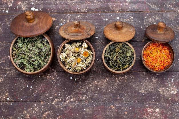 Una vista superior de condimentos secos de diferentes colores dentro de tazones sobre el fondo marrón verde menta seca