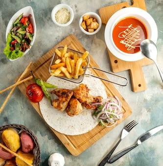Vista superior de la configuración del almuerzo con pollo, kebab, papas fritas, sopa de tomate y ensalada