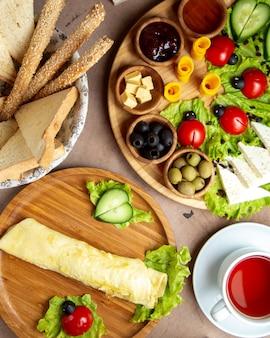 Vista superior de la configuración del desayuno con una taza de té de tortilla y otros platos
