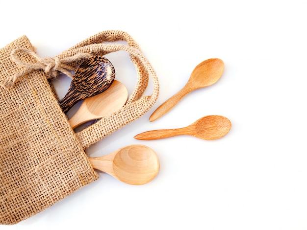 Vista superior conjunto de cuchara de madera en bolsa de saco, materiales naturales para la salud aislado sobre superficie blanca.