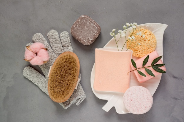 Vista superior del conjunto de cuidados de belleza, esponjas y cepillo de masaje de jabón y una toallita en forma de guante sobre fondo gris.