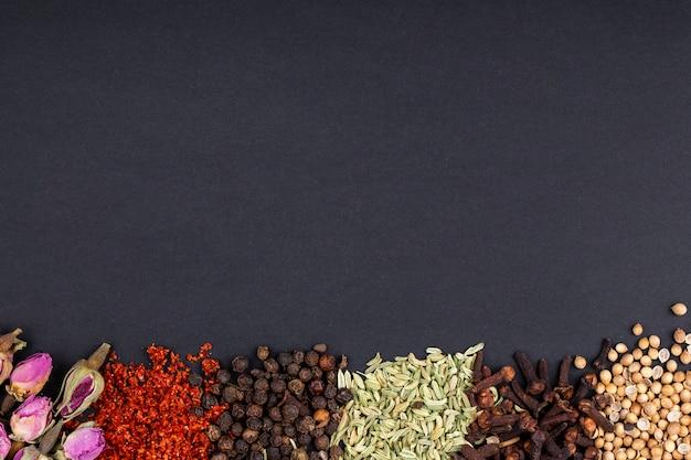 Vista superior de un conjunto de especias y hierbas, capullos de rosa de té, hojuelas de chile rojo, granos de pimienta negra, semillas de anís y clavo sobre fondo negro con espacio de copia