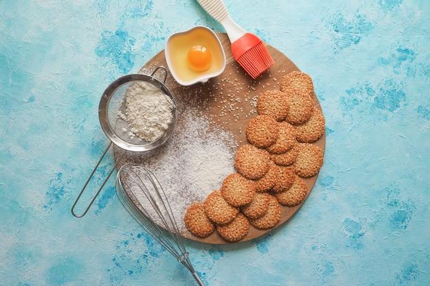Vista superior del conjunto de productos para cocinar galletas, utensilios de cocina y varias galletas redondas con sésamo en una mesa de madera azul