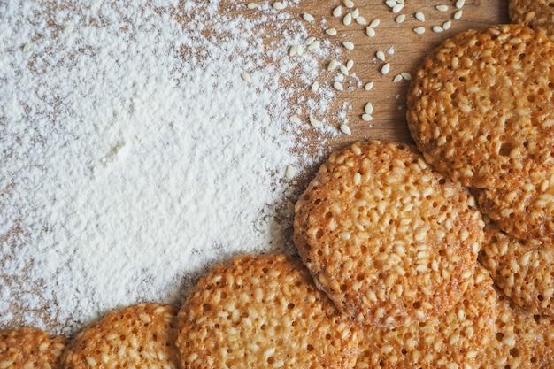 Vista superior del conjunto de productos para cocinar galletas, utensilios de cocina y varias galletas redondas con sésamo.