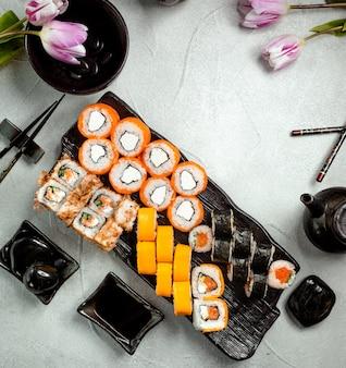 Vista superior del conjunto de rollos de sushi servido con salsa de soja