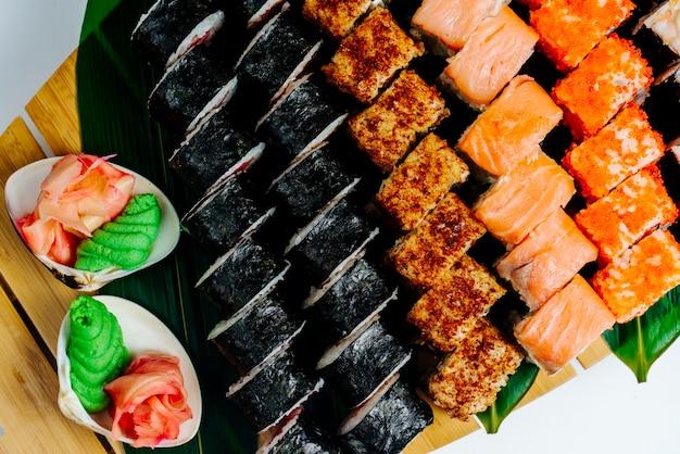 Vista superior del conjunto de rollos de sushi servido con wasabi y jengibre