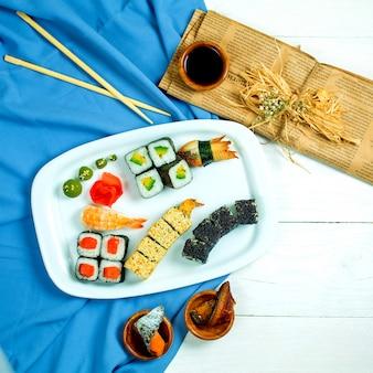 Vista superior del conjunto de sushi y maki con salsa de soja en azul y blanco