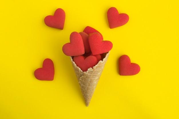 Vista superior del cono de helado con galletas en forma de corazón rojo en el amarillo