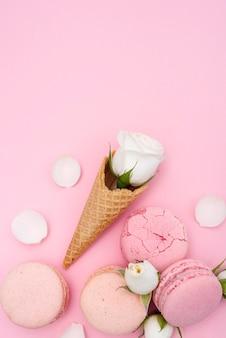 Vista superior del cono de helado con rosas y macarons