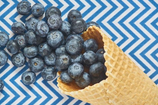 Vista superior del cono de waffle con arándanos en textil azul