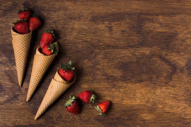Vista superior conos de helado con fresas
