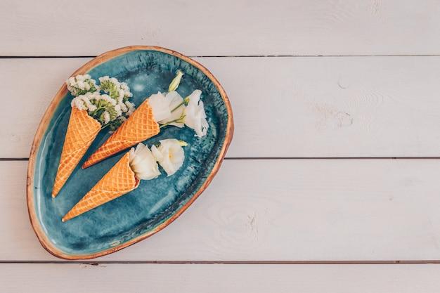 Vista superior de conos de helado en plato viejo con flores en madera blanca