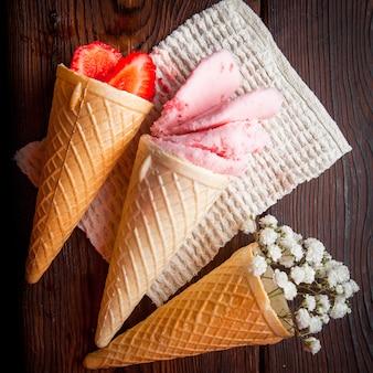 Vista superior conos de waffle con fresa y helado y gypsophila en servilletas de trapo