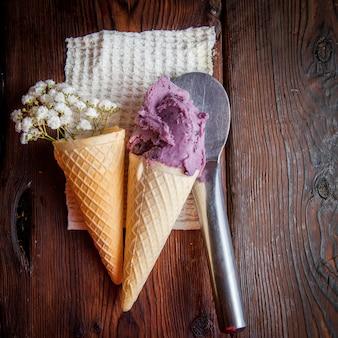 Vista superior conos de waffle con helado de arándanos y cuchara de helado y gypsophila en servilletas de trapo