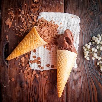 Vista superior conos de waffle con helado de chocolate y chips de chocolate y gypsophila en servilletas de trapo