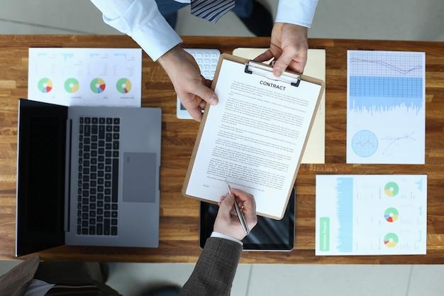 Vista superior del contrato de firma de la mano del empresario. gente de negocios haciendo rentable negociación internacional. laptop, documentos con datos estadísticos en el lugar de trabajo. concepto de reuniones y negociaciones