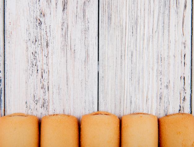 Vista superior cookies con mermelada en la parte inferior con espacio de copia sobre fondo blanco de madera
