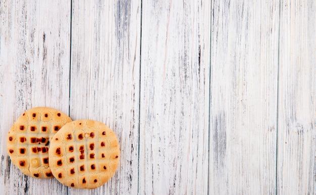 Vista superior cookies con relleno a la izquierda con espacio de copia sobre fondo blanco de madera