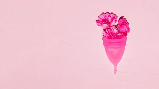 Vista superior copa menstrual con flores