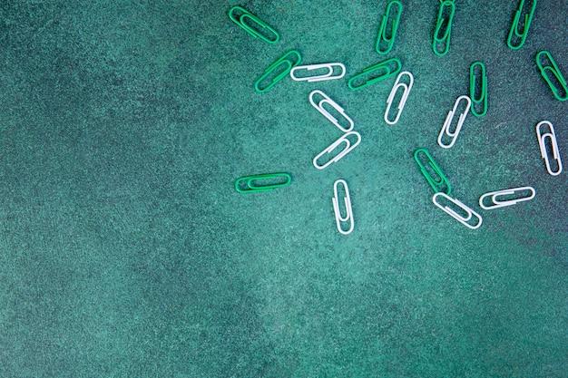 Vista superior copia espacio clips de papel verde y blanco sobre un fondo verde
