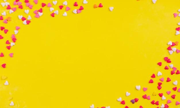 Vista superior copia espacio dulces multicolores en forma de corazón sobre un fondo amarillo
