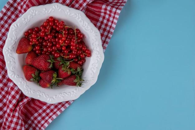 Vista superior copia espacio fresas con grosella roja en un plato con una toalla de cocina roja sobre un fondo azul claro