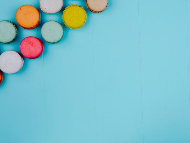 Vista superior copia espacio macarons multicolores sobre un fondo azul.