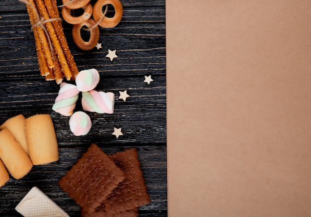 Vista superior copia espacio malvaviscos con galletas de chispas de chocolate estrellas y con el cuaderno sobre fondo de madera negra