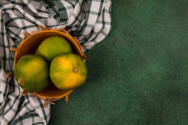 Vista superior copia espacio mandarinas verdes en canasta con toalla a cuadros en pared verde