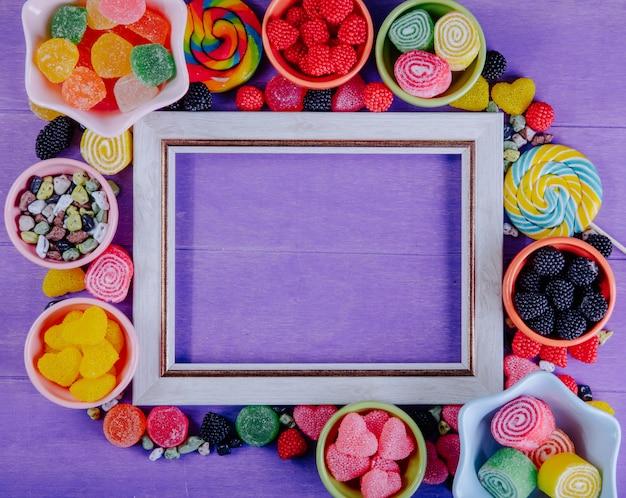 Vista superior copia espacio marco gris con mermelada multicolor piedras de chocolate y carámbanos de colores en platillos para mermelada sobre un fondo morado