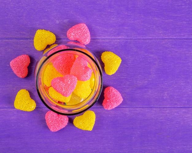 Vista superior copia espacio mermelada amarilla y rosa en forma de corazón en un frasco sobre un fondo morado
