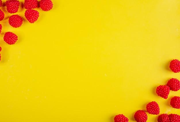 Vista superior copia espacio mermelada en forma de frambuesas sobre un fondo amarillo